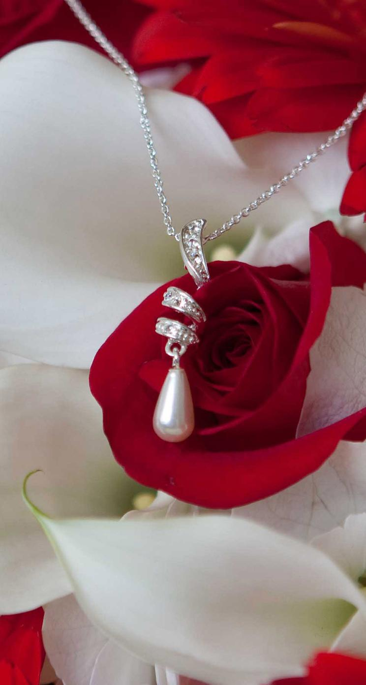 A Necklace With A Pearl On The White And Red Flowers Wallpaper