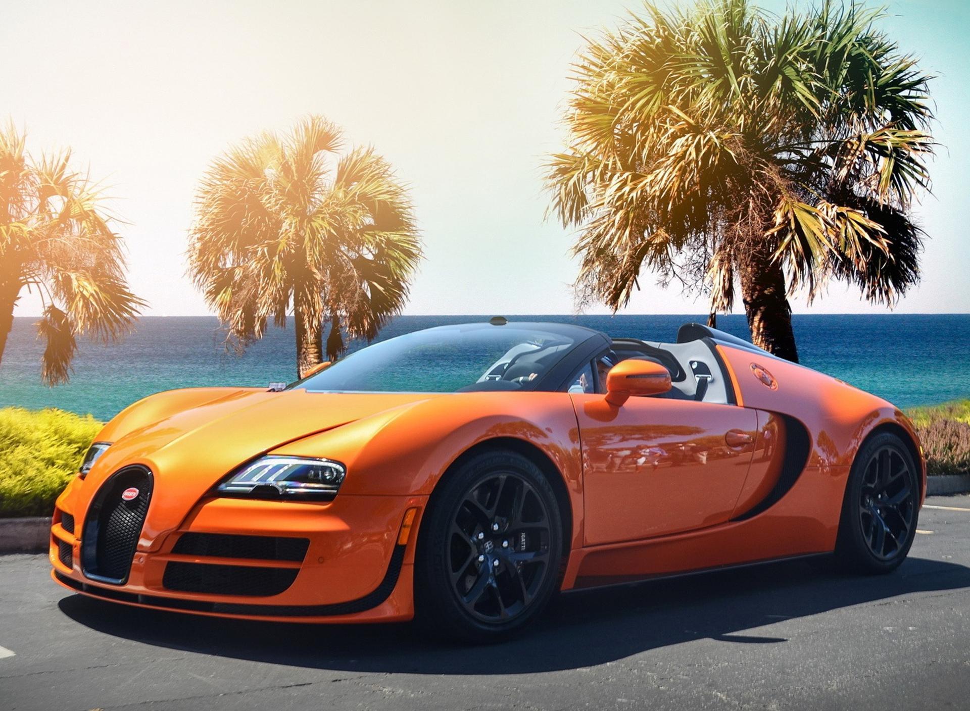 Gorgeous Orange Bugatti Veyron W16 On The Shore Of Sea Wallpaper