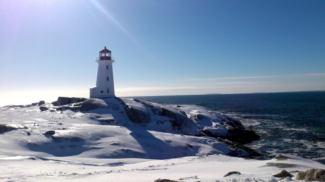 Download Wallpaper Winter time on the sea - lighthouse in the sun