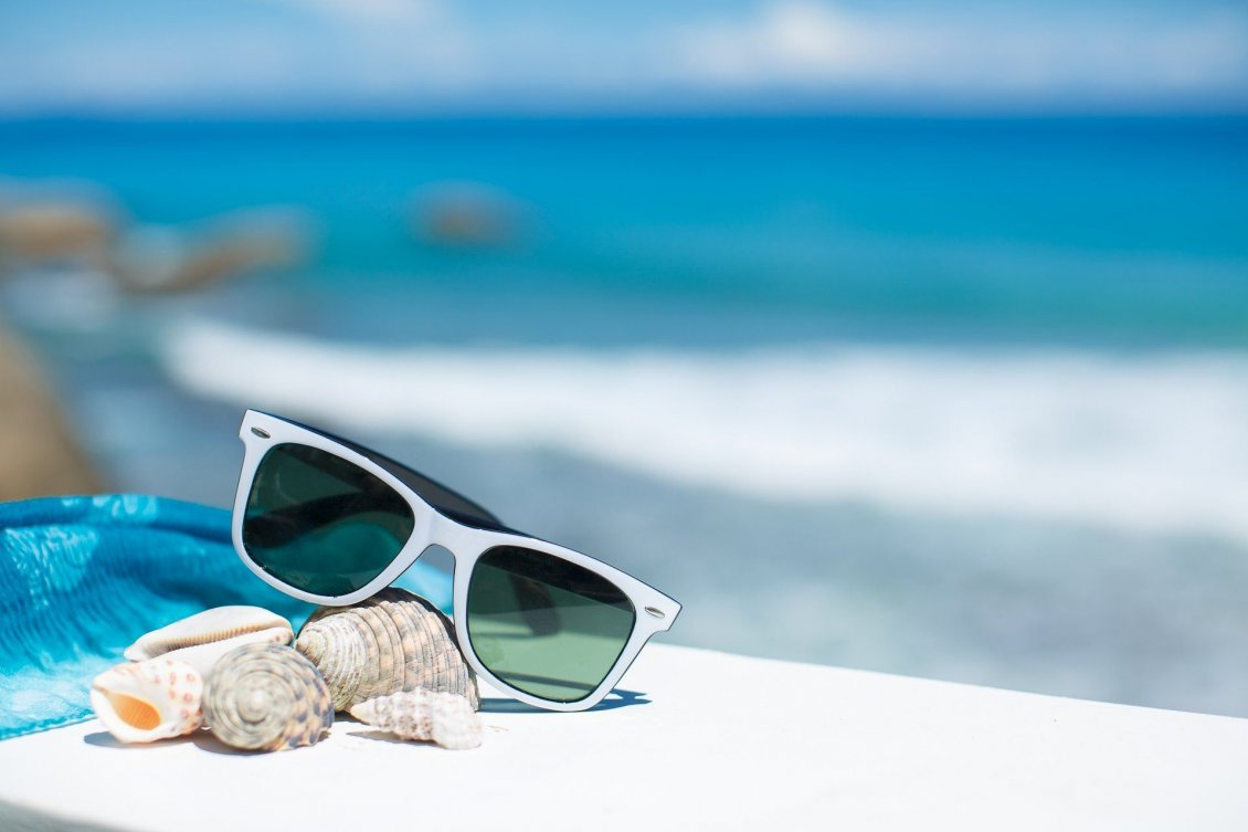 Download Wallpaper Sunglasses and shells -Wonderful blurry ocean on background