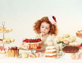 The girl looks long at cakes on the table