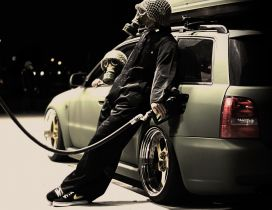 Man with gas mask getting gas at a gas station