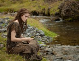 Emma Watson sitting on the grass on the river