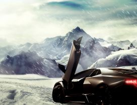 Brown Lamborghini in the snow between the mountains