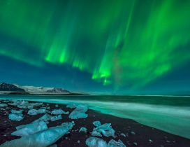 Green aurora borealis over the ocean