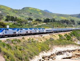 Gray and blue train on foothills