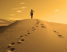 One man and his traces in the sand of desert