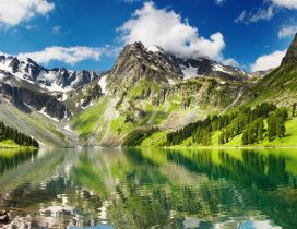 Green and white mountains reflected in the lake water