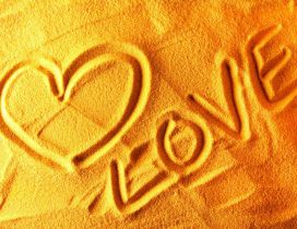 A heart and love letters in the sand