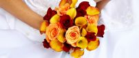 A bridal bouquet made of yellow callas and red roses