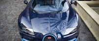 Blue Bugatti Veyron front view on sidewalk