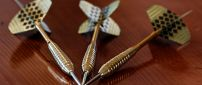 Golden darts piece on the table - HD macro wallpaper