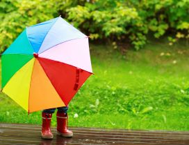 Little kid is playing in the rain with a colorful umbrella