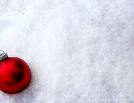Shiny red Christmas ball in the white and cold snow