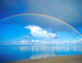 Beautiful rainbow over the blue ocean water - Sunny summer
