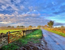 Sunrise over the country side road and fence