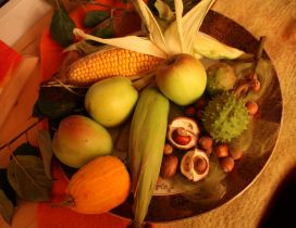 Autumn goodies in one plate - apples, nuts and corn