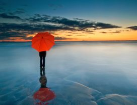 Abstract photo - Man with orange umbrella on a frozen water