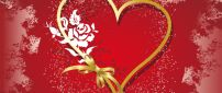 Golden heart made with a ribbon on a red background - Love