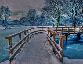 Wonderful frozen bridge over a frozen lake with blue water