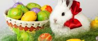 Big red ribbon on a fluffy Easter bunny - Colored eggs