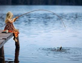 Little blonde girl fishing in a lake - Wonderful photo